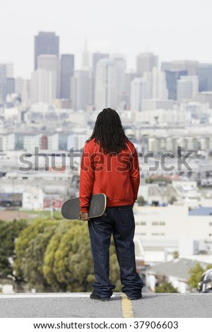African American Boy Holding Skateboard Looking at City View