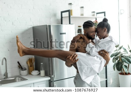 african american boyfriend holding girlfriend at kitchen