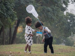 African American boys and girls catch insects in the forest on adventure camping travel trips. Preschool kids catching bugs with net. Adventure kindergarten day trip into wild nature.