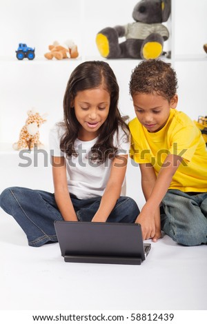 african american brother and sister playing laptop computer - stock photo