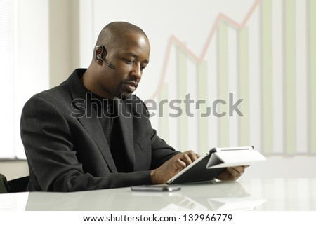 African American business man on his blue tooth using tablet.