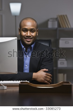 African American business man smiling at camera, sitting at desk with computer monitor. Vertical