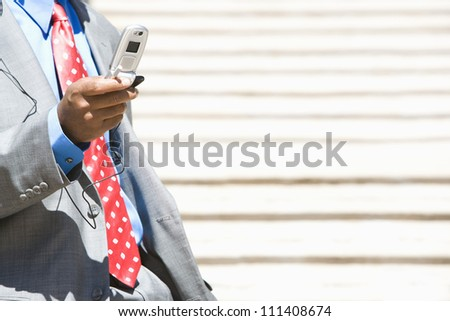 African American business man text messaging through cell phone