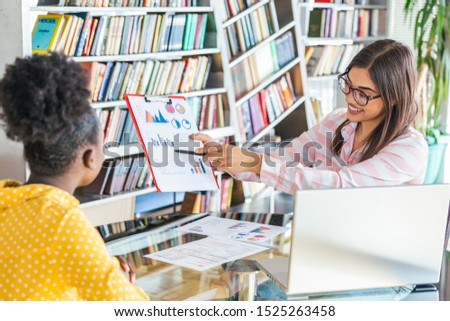 African American business woman holding papers and smiling.Young team of coworkers making great business discussion in modern coworking office.Teamwork people concept. #1525263458