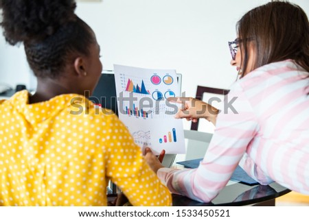 African American business woman holding papers and smiling.Young team of coworkers making great business discussion in modern coworking office.Teamwork people concept. #1533450521