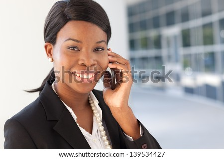 African-american business woman on cell phone, smiling, talking, in suit and pearls outside a modern building. - stock photo