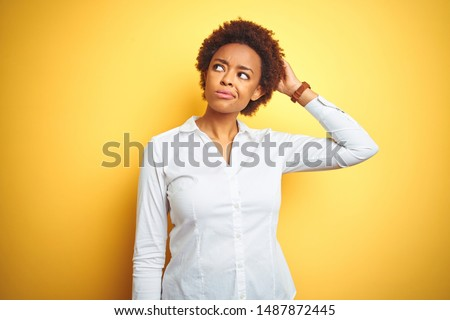 African american business woman over isolated yellow background confuse and wondering about question. Uncertain with doubt, thinking with hand on head. Pensive concept.