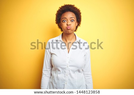 African american business woman over isolated yellow background puffing cheeks with funny face. Mouth inflated with air, crazy expression.