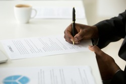 African american businessman agree to make deal signing business contract concept, black man hand putting signature on commercial business paper, filling legal document at work, close up view