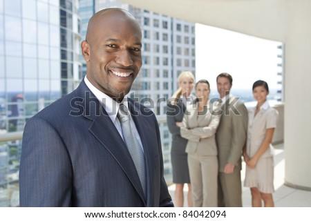 African American businessman and an interracial group of business men & women, businessmen and businesswomen team
