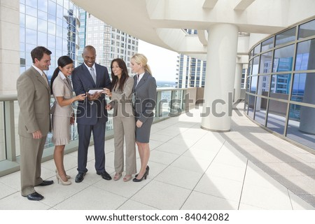 African American businessman and Chinese Asian businesswoman using tablet computer with interracial group of business men & women team.