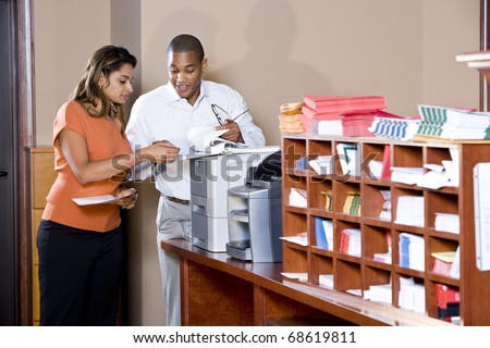 African American businessman and Indian businesswoman working together in office