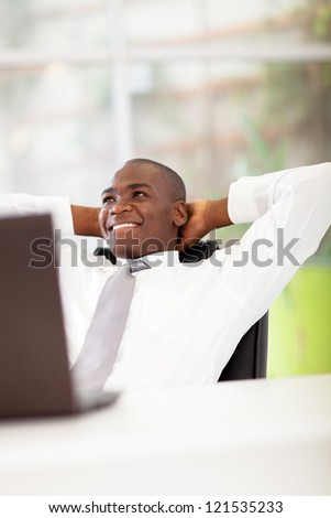 african american businessman daydreaming in office
