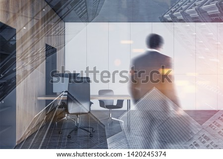 African American businessman entering modern open space office with white and concrete walls, wooden bookcases and tables. Toned image double exposure blur #1420245374