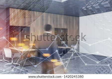 African American businessman entering modern open space office with white and concrete walls, wooden bookcases and tables. Double exposure of graphs. Stock market concept. Toned image blur #1420245380