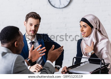 african american businessman gesturing during discussion with smiling multicultural business partner and interpreter, blurred foreground Сток-фото ©