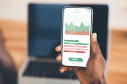 African american businessman hand holding mobile phone with analytics app over laptop, creative image. Unrecognizable black manager using financial application on smartphone while working in office