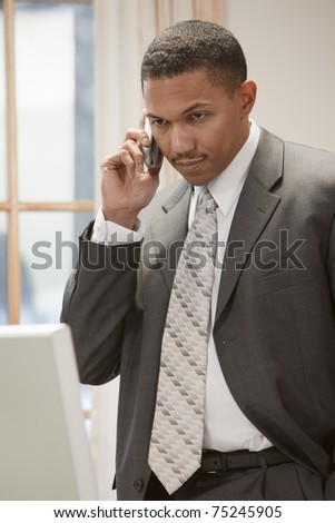 African American businessman on the phone standing in his office