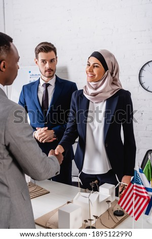 african american businessman shaking hands with happy arabian business partner near maquette of green energy station and international flags Photo stock ©