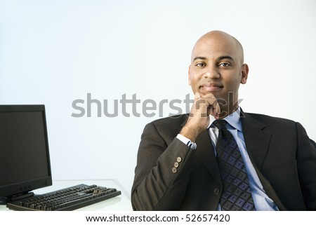 African American businessman sitting at office desk smiling.