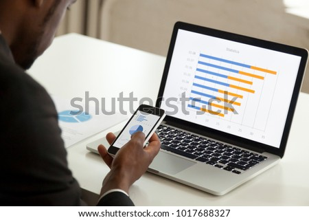African american businessman using devices for business, black office worker holding smartphone working with laptop and mobile phone, corporate statistics apps and software, over the shoulder view