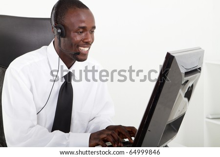 African American businessman with headset sitting at office desk
