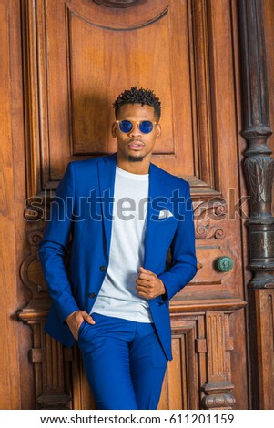 African American Businessman with little goatee working in New York, wearing blue suit, unbuttoned, white collarless shirt, blue sunglasses, standing against vintage office door, thinking.