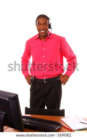 African American businessman working  in a corporate office standing behind his desk and talking on the telephone through a wireless headset