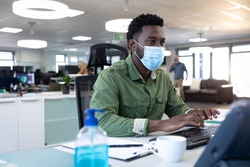African American businessman working in modern office wearing face mask, sitting at desk using computer. Hygiene and social distancing in workplace during Coronavirus Covid 19 pandemic.