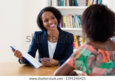 African american businesswoman and applicant talking about contract at job interview at office