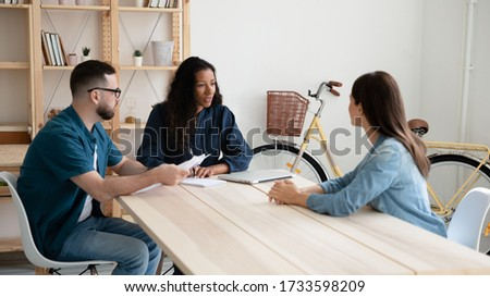 African american businesswoman and businessman with cv interviews new woman applicant. Confident young diverse team hr managers holding resume in negotiation with job seeker in office at hire meeting.