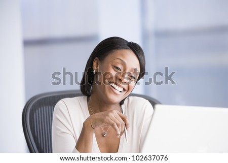 African American businesswoman smiling at laptop