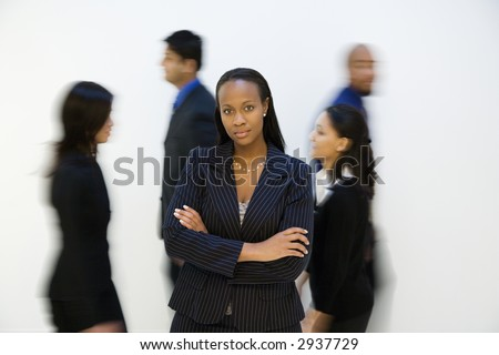 African-American businesswoman standing with arms crossed while others walk by. - stock photo