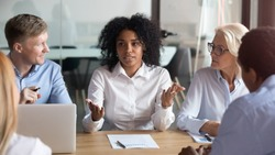 African american businesswoman talking to clients make business offer explain deal benefit convince diverse partners at group negotiation meeting, mixed race manager consult customers sell services