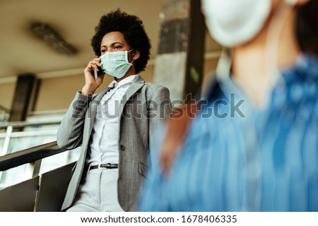 African American businesswoman wearing face mask against viruses while walking through railroad station corridor.