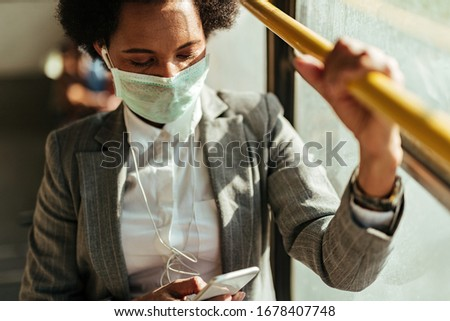 African American businesswoman wearing face mask while texting on cell phone and traveling to work by bus.