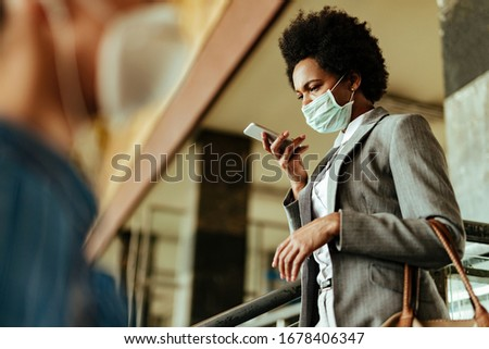 African American businesswoman wearing face mask while using voice assistant on mobile phone at public train station.