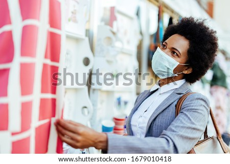 African American businesswoman wearing protective mask on her face while being at street market.