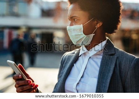 African American businesswoman wearing protective mask on her face while using smart phone in the city.