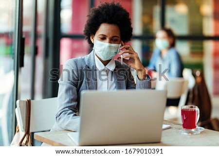 African American businesswoman wearing protective mask while communicating on mobile phone and working on laptop in a cafe.