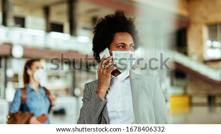 African American businesswoman wearing protective mask while communicating on mobile phone at the airport.