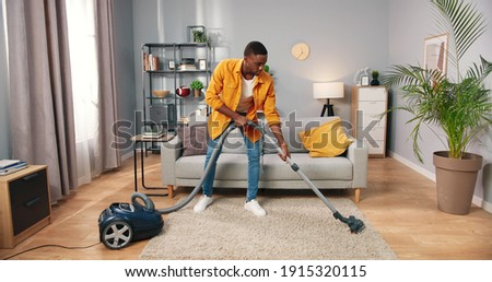 African American busy handsome young guy vacuuming cozy living room doing housework, male cleaning house using vacuum keeping home clean, housekeeper, everyday life concept