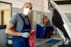African American car mechanic with face mask working in auto repair shop during coronavirus pandemic.