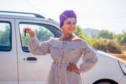 African american caucasian woman in a purple turban head posing with her new car showing the key outdoors, outside in summer day beach ocran sea on background.indian girl ride travel