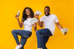 African american cheerful couple dancing with money in their hands, lifting legs up