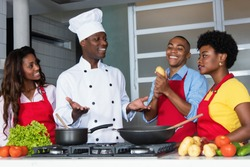African american chef teaching women and men to cook at kitchen