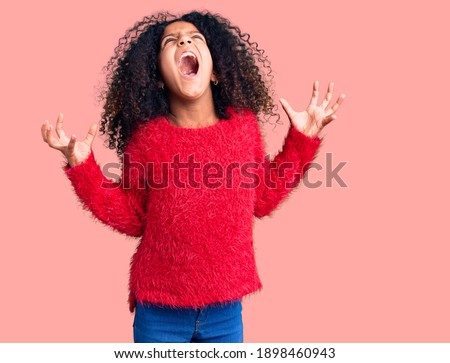 African american child with curly hair wearing casual winter sweater crazy and mad shouting and yelling with aggressive expression and arms raised. frustration concept.  Stock photo ©