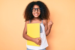 African american child with curly hair wearing glasses and holding book screaming proud, celebrating victory and success very excited with raised arm