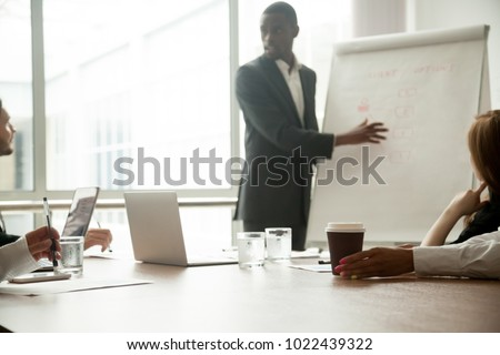 African american coach gives presentation for businesspeople working with flipchart, diverse multiracial team sitting at conference meeting table listening to speaker presenting new project in office