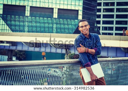 African American college student studying in New York. Wearing blue shirt, glasses, bracelets, holding laptop computer, a young black man standing in business district with high buildings, smiling.  #314982536